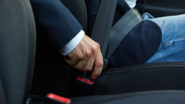 Driver sits in the car and fastens his seat belt, safe driving tips