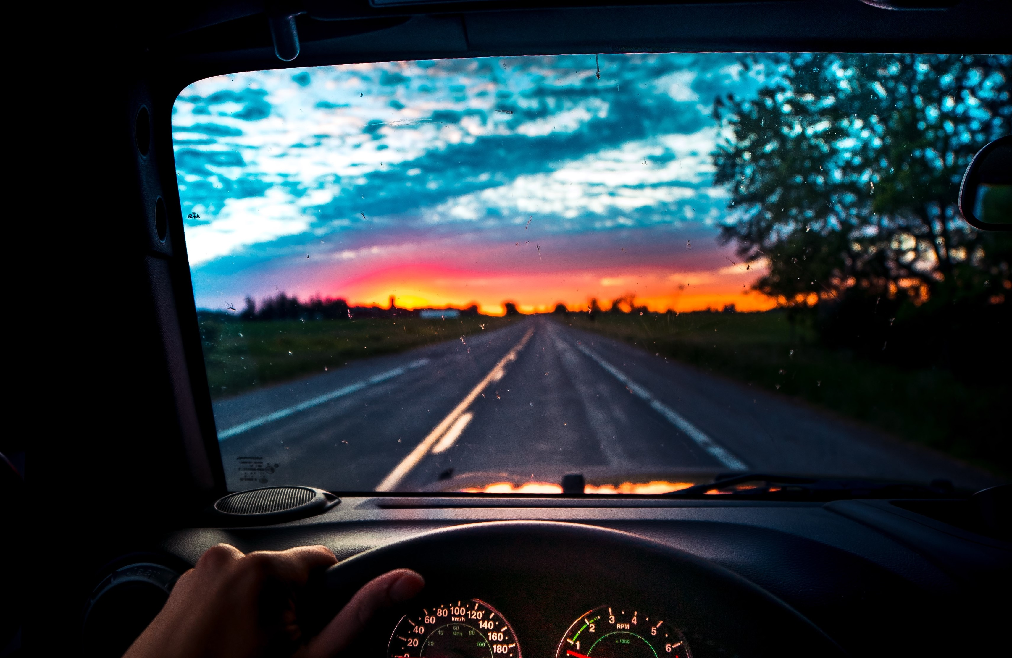 a car driving down the highway towards a sunset