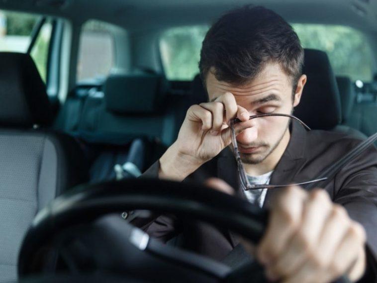 sleepy young man driving rubbing his eyes