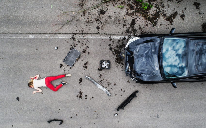 woman lying on the road after car accident